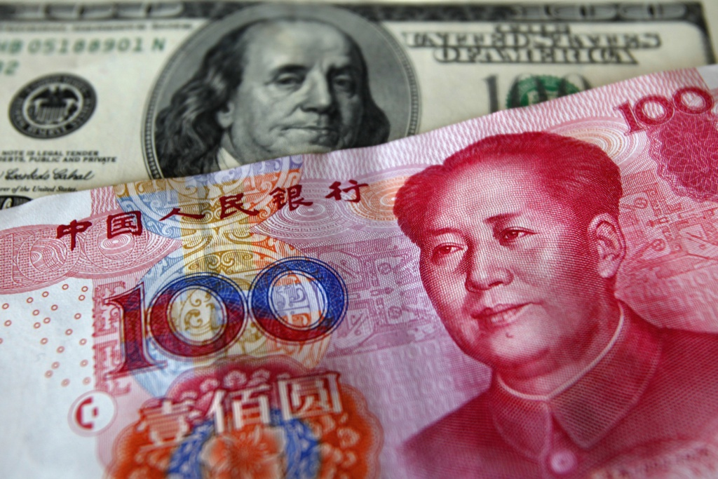 A yuan banknote is displayed next to a U.S. dollar banknote (back) for the photographer at a money changer inside the Taoyuan International Airport March 18, 2010. China faces important negotiations over its exchange rate in coming weeks, the U.S. ambassador to China said on Thursday, adding that it was not just the United States that wanted action on the Chinese yuan.   REUTERS/Nicky Loh (TAIWAN - Tags: BUSINESS)
